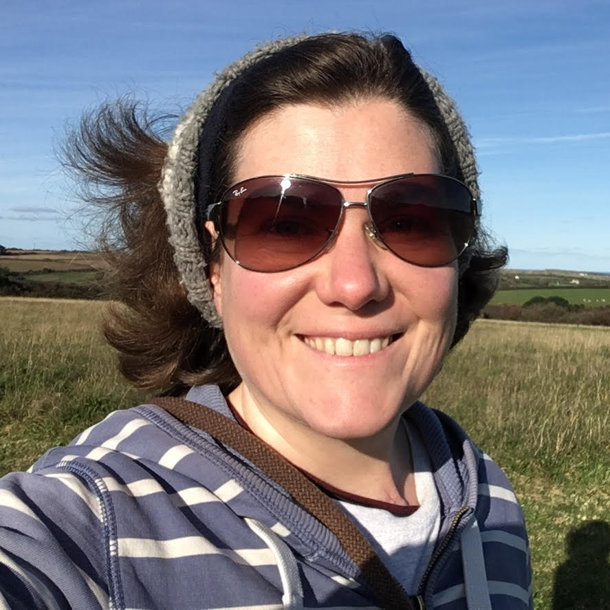 Photo of Beccy Stirrup, a red-faced woman with medium-length brown hair. She is pictured outdoors, wearing sunglasses and hair pulled back.