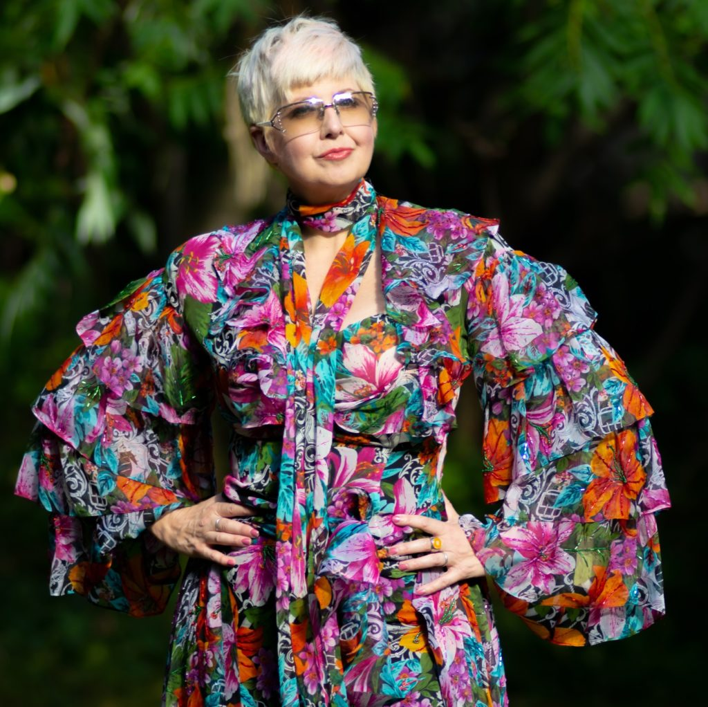 Photo of actor Mama Bang Bang, aka Jessie Baade - a three-quarters shot of a woman with short white hair, large tinted glasses, wearing a colourful dress.